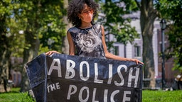 BROOKLYN, NEW YORK, UNITED STATES - 2020/07/26: A participant holding an Abolish The Police banner at the protest. Brooklynites gathered at Irving Square Park for a march in the streets of Bushwick, demanding justice for all victims of police brutality, bringing light to the situation in Portland, also to make a loud call to defund the NYPD and invest in communities. Street Riders NYC participated by sending bikes to act as a buffer and shield protesters from cars and police.