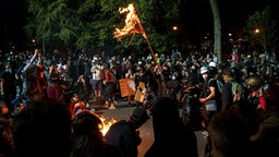"""A demonstrator burns an American flag outside the Mark O. Hatfield United States Courthouse late Friday night during the protest on July 31, 2020 in Portland, Oregon. - US federal officers will stay in the protest-wracked city of Portland until local law enforcement officials finish a """"cleanup of anarchists and agitators,"""" the US President said."""