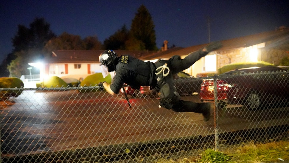 PORTLAND, OR - AUGUST 1: A Portland police officer jumps a fence to pursue a protester through suburban streets after dispersing a crowd of about 200 people from in front of the Multnomah County Sheriffs Office on August. 1, 2020 in Portland, Oregon. Protest actions spread to East Portland on Saturday as federal officers began a phased withdrawal from the more central located U.S. courthouse.
