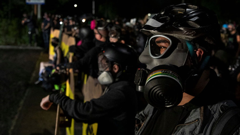 Protesters are seen during a standoff at a Portland police precinct in Portland, Oregon on August 15, 2020. Protests have continued for the 80th consecutive night in Portland since the killing of George Floyd. (Photo by Paula Bronstein/Getty Images )