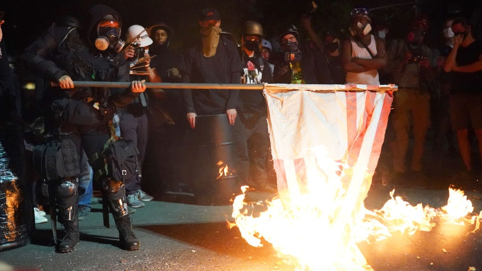 PORTLAND, OR - AUGUST 1: A protester burns an American flag in front of the Mark O. Hatfield U.S. Courthouse in the early morning on August 1, 2020 in Portland, Oregon. Friday was the second night in a row without police intervention, following weeks of clashes between federal officers and protesters in Portland. (Photo by Nathan Howard/Getty Images)