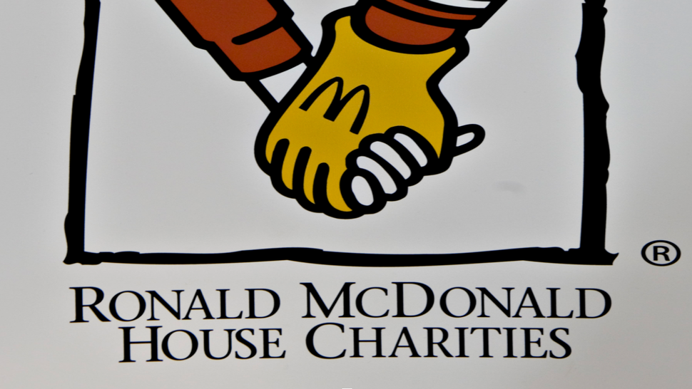 """A Ronald McDonald House Charities logo sits on display on the sidelines of the Berkshire Hathaway annual meeting in Omaha, Nebraska, U.S., on Saturday, May 1, 2010. Ronald McDonald house exists to """"create, find and support programs that directly improve the health and well being of children,"""" according to its website."""