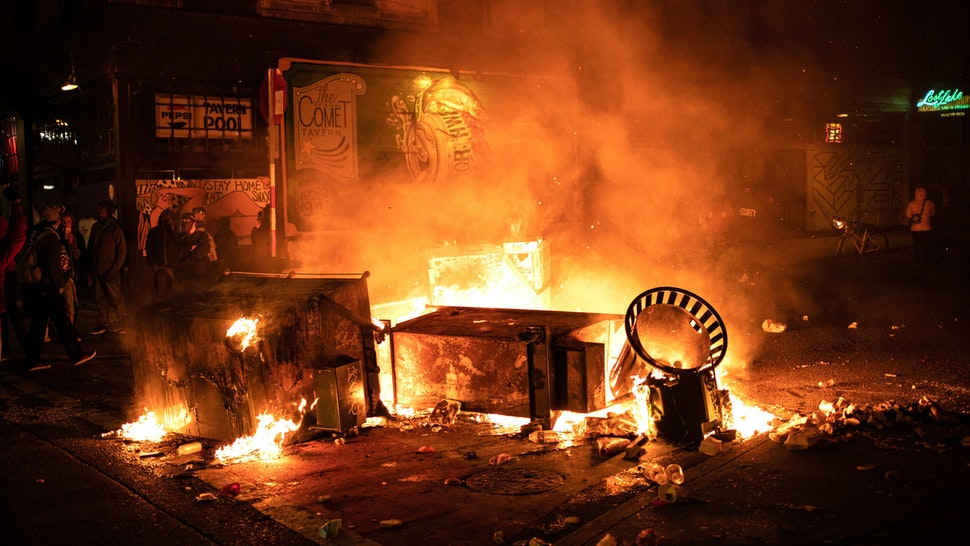 SEATTLE, WA - JUNE 08: A fire burns in the street after demonstrators clashed with law enforcement near the Seattle Police Departments East Precinct shortly after midnight on June 8, 2020 in Seattle, Washington. Earlier in the evening, a suspect drove into the crowd of protesters and shot one person, which happened after a day of peaceful protests across the city. Later, police and protesters clashed violently during ongoing Black Lives Matter demonstrations following the death of George Floyd.