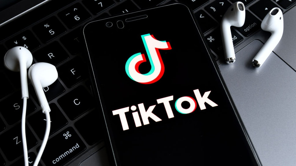 HAIKOU, HAINAN, CHINA - 2020/08/23: In this photo illustration, a TikTok logo seen displayed on a smartphone with a computer in the background. ByteDance, parent company of popular video-sharing app TikTok on Sunday confirmed it would be filing a lawsuit on Monday local time against the Trump administration over the executive order signed by President Donald Trump banning its service in the United States.