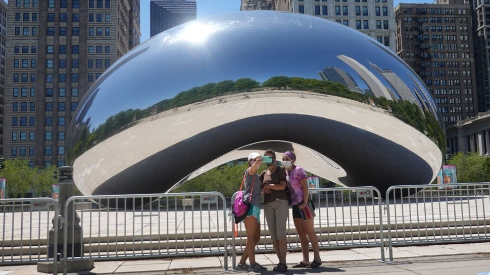 CHICAGO, ILLINOIS - JUNE 15: Visitors take pictures in front of the Cloud Gate sculpture in Millennium Park on June 15, 2020 in Chicago, Illinois. The park, which had been closed to visitors to help curtail the spread of the coronavirus COVID-19, partially reopened, with restrictions, to the public today. The park located in downtown Chicago is the most visited tourist attraction in the Midwest, attracting more than 12 million visitors annually. (Photo by