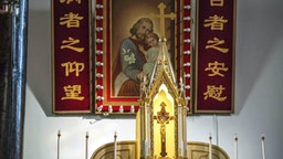 A cross with Jesus (front) and a painting with Joseph and Jesus (back) are seen inside St. Joseph's church, also known as Wangfujing church, in Beijing on January 25, 2018.