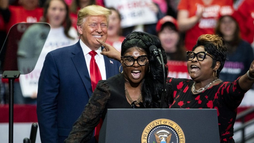 """Social Media influencers and video bloggers Lynnette """"Diamond"""" Hardaway, center, and Rochelle """"Silk"""" Richardson, right, speak as U.S. President Donald Trump smiles during a rally in Charlotte, North Carolina, on Monday, March 2, 2020. Trump told reporters in the Oval Office on Monday that holding campaign rallies with thousands of attendees is """"very safe"""" despite recent cases of the virus in the U.S. Photographer:"""