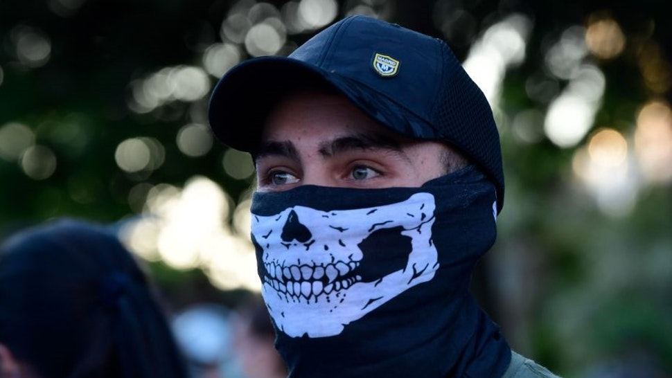 A demonstrator covers his face with a neck gaiter as he takes part in a demonstration against the government's handling of the coronavirus crisis, on May 20, 2020, in Alcorcon, near Madrid. - Spain's prime minister won parliamentary backing extend the lockdown for another two weeks today, despite opposition from his rightwing opponents and protests against his minority coalition government. It was the fifth time the state of emergency has been renewed, meaning the restrictions will remain in force until June 6 in a measure passed by 177 votes in favour, 162 against and 11 abstentions. (Photo by JAVIER SORIANO / AFP) (Photo by