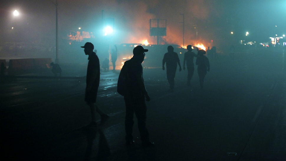 KENOSHA, WI - AUGUST 24: People walk trough smoke filled street from near by burinng buildings as demonstrators protest the police shooting of Jacob Blake on Monday, August 24, 2020 in Kenosha, Wisconsin. Blake was shot in the back multiple times by police officers responding to a domestic dispute call yesterday.