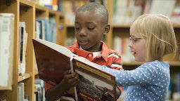 Boy and girl classmates sharing book in library