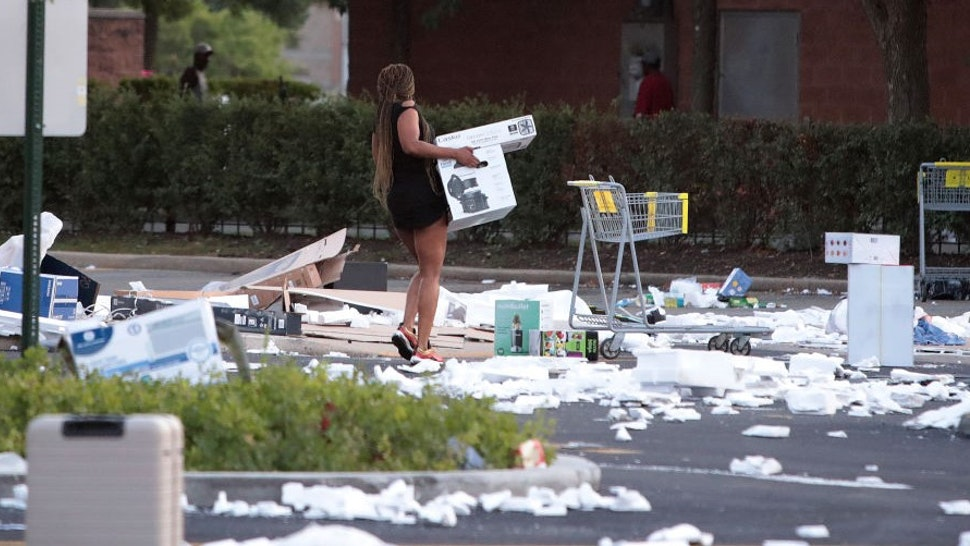 CHICAGO, ILLINOIS - AUGUST 10: A person carries a box near a looted Best Buy store seen after parts of the city had widespread looting and vandalism, on August 10, 2020 in Chicago, Illinois. Police made several arrests during the night of unrest and recovered at least one firearm. (Photo by
