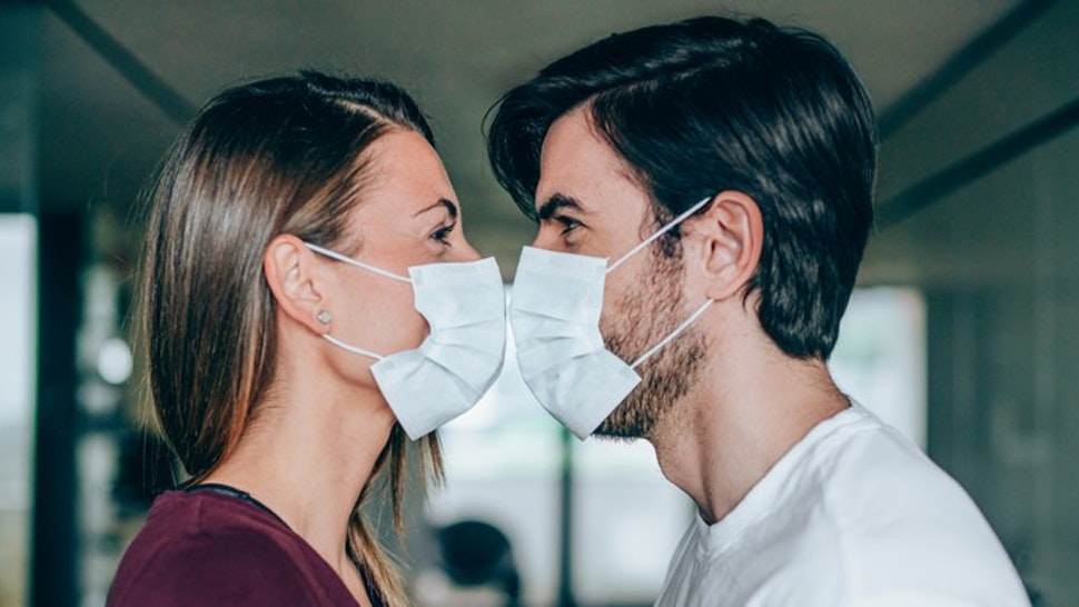 Beautiful happy young couple wearing protective face masks and kissing each other. Side view of young man and young woman in medical masks kissing while they are in home isolation during coronavirus/COVID-19 quarantine.