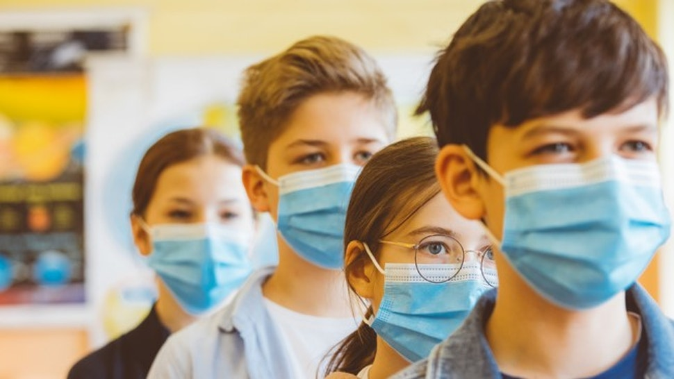 Group of student at a high school stands among the students. All students wearing blue N95 Face masks waiting in line.