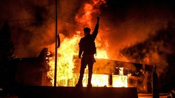 TOPSHOT - A protester reacts standing in front of a burning building set on fire during a demonstration in Minneapolis, Minnesota, on May 29, 2020, over the death of George Floyd, a black man who died after a white policeman kneeled on his neck for several minutes. - Violent protests erupted across the United States late on May 29 over the death of a handcuffed black man in police custody, with murder charges laid against the arresting Minneapolis officer failing to quell seething anger.