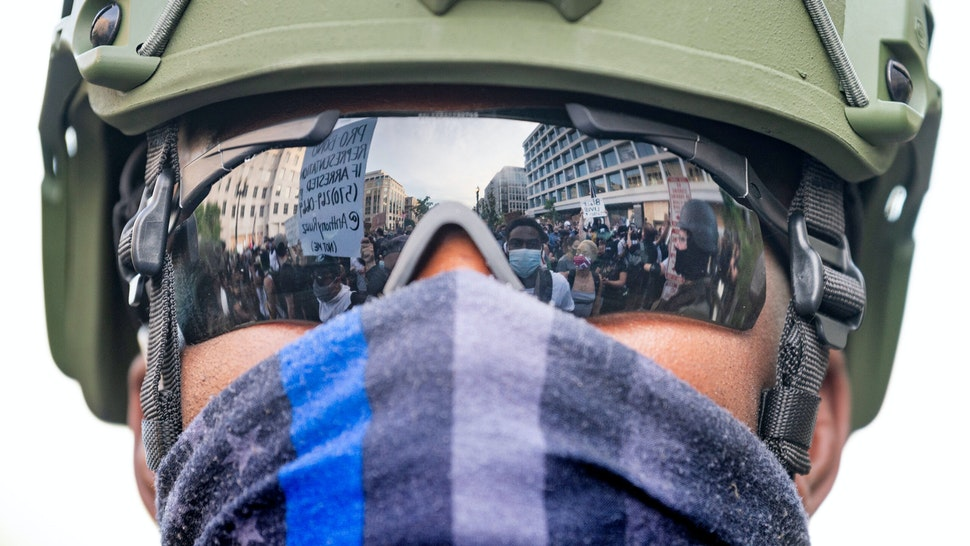Protesters are reflected in the glasses of an US Army National Guard member as they demonstrate the death of George Floyd near the White House on June 3, 2020, in Washington, DC. - Former Minneapolis police officer Derek Chauvin, who kneeled on the neck of George Floyd who later died, will now be charged with second-degree murder, and his three colleagues will face charges of aiding and abetting second-degree murder, court documents revealed on June 3.