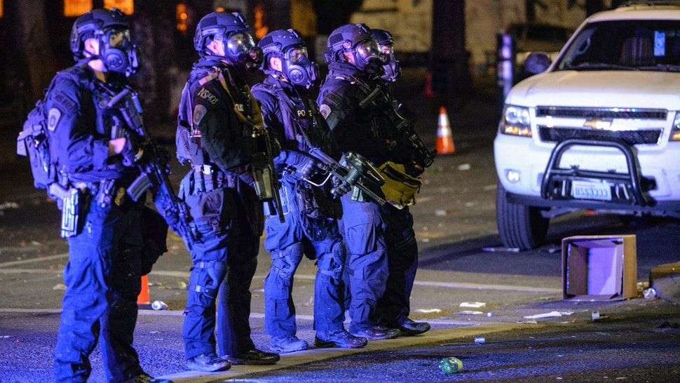 "Security officials form a line across a street in Portland, Oregon early July 26, 2020, as protests continue across the United States following the death in Minneapolis of unarmed African-American George Floyd. - Police and federal agents fired tear gas and forcefully dispersed protesters in the US city of Portland, amid President Donald Trump's heavily-criticized ""surge"" of security forces to major cities. The city, the biggest in the state of Oregon, has seen nightly protests against racism and police brutality for nearly two months, initially sparked by the death of unarmed African American George Floyd at the hands of police in Minnesota"