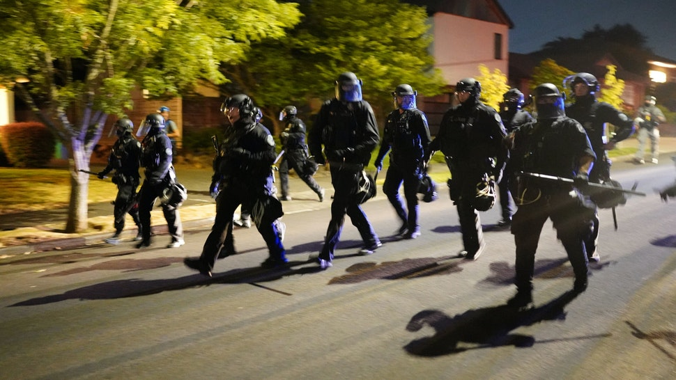 PORTLAND, OR - AUGUST 1: Portland police officers pursue a crowd of about 200 protesters after dispersing the group from in front of the Multnomah County Sheriffs Office on August. 1, 2020 in Portland, Oregon. Protest actions spread to East Portland on Saturday as federal officers began a phased withdrawal from the more centrally located U.S. courthouse.