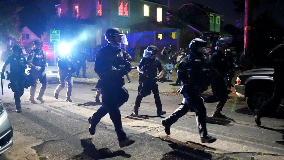 PORTLAND, OR - AUGUST 14: Portland police run through a residential neighborhood while dispersing a crowd of about 400 protesters on August 14, 2020 in Portland, Oregon. The Portland Police Bureau changed tactics Friday night, blocking streets well before the protest of about 400 people could reach the Portland Police Association building.