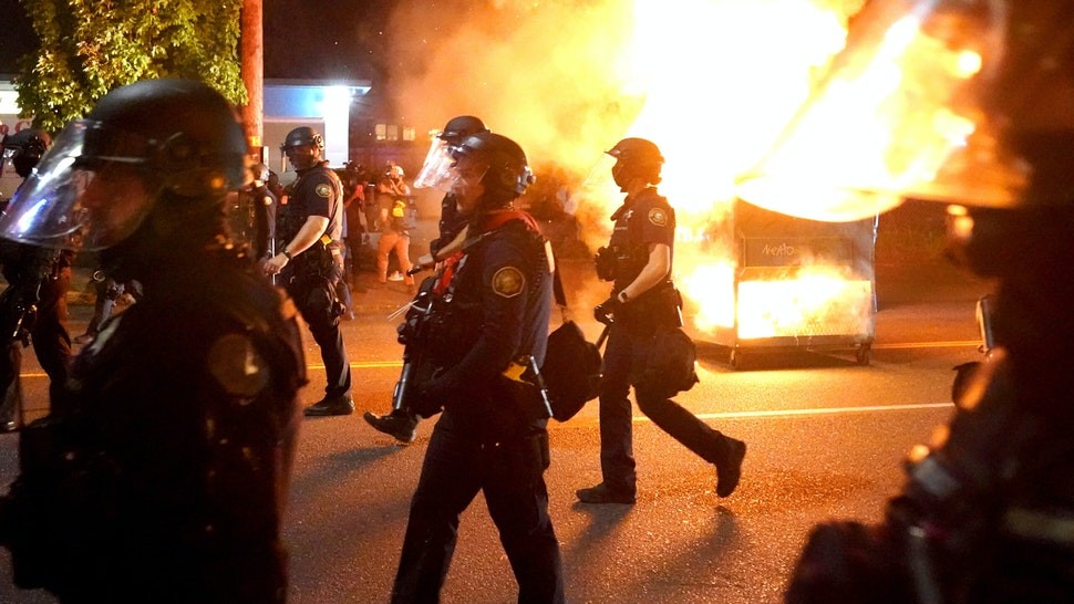 PORTLAND, OR - AUGUST 14: Portland police walk past a dumpster fire during a crowd dispersal on August 14, 2020 in Portland, Oregon. The Portland Police Bureau changed tactics Friday night, blocking streets well before the protest of about 400 people could reach the Portland Police Association building.