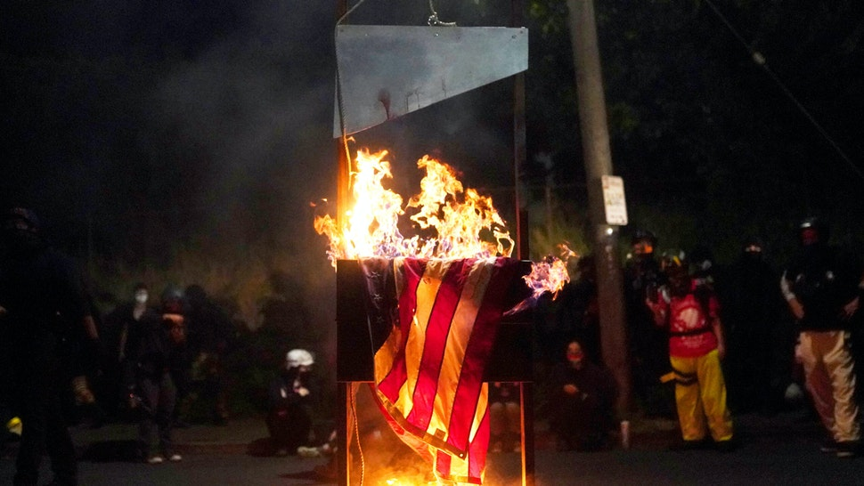 PORTLAND, OR - AUGUST 22: An American flag burns in front of the Multnomah County Sheriffs Office on August 22, 2020 in Portland, Oregon. Hundreds of protesters clashed with police Saturday night following a rally in east Portland.