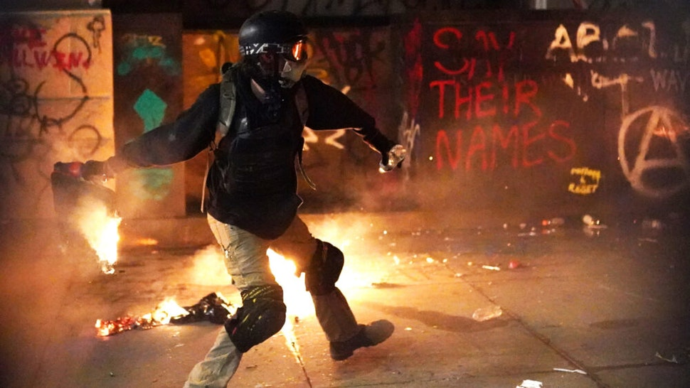 A protester throws flaming trash toward the Mark O. Hatfield U.S. Courthouse after breaking through a newly-reinforced perimeter fence on July 22, 2020 in Portland, Oregon. The night marked 56 days of protests in Portland following the death of George Floyd in police custody.