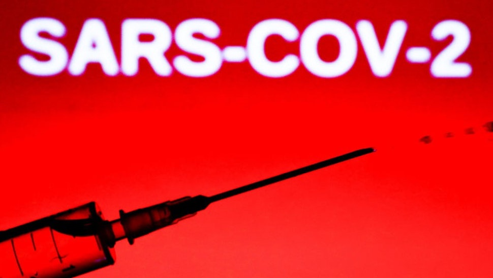 In this illustration photo a medical syringe is seen with 'sars-cov-2' sign in the background. Picture taken in Krakow, Poland, on June 9, 2020. (Photo by
