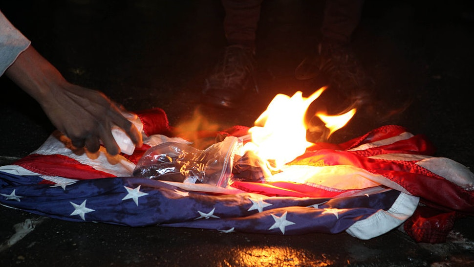 NEW YORK - NOVEMBER 9: Protesters burn the Stars and Stripes American Flag outside Trump Tower as Donald Trump is elected President on November 9, 2016 in New York City. (Ruaridh Connellan/BarcroftImages / Barcroft Media via Getty Images)