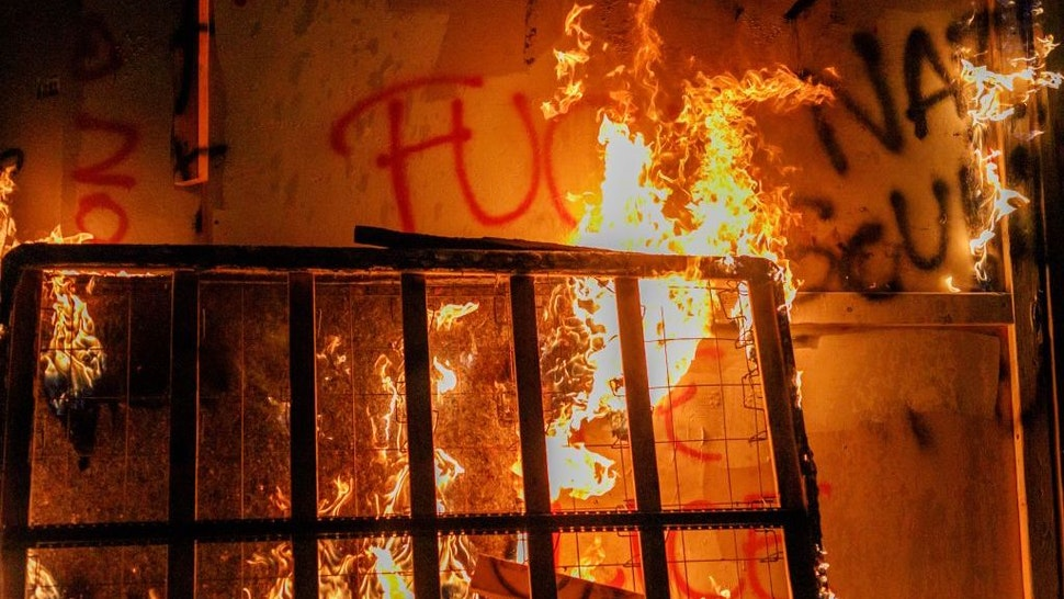About two hundred persons protesting police brutality spray graffiti and start fires at the Portland Police Union building, in Portland, Oregon, United States on August 28, 2020, the 93rd day of consecutive protests. Police declared a riot and arrested many people. (Photo by John Rudoff/Anadolu Agency via Getty Images)