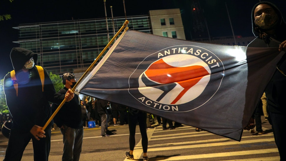 """NEW YORK, USA - SEPTEMBER 6: A man holds an anti-fascism flag as hundreds of demonstrators gather and march to the City Public Safety Building over Daniel Prudeâs death in Rochester, New York, United States on September 6, 2020. Daniel Prude, an unarmed black man who died after being arrested and being placed a """"spit hood"""" over his head by Rochester police."""