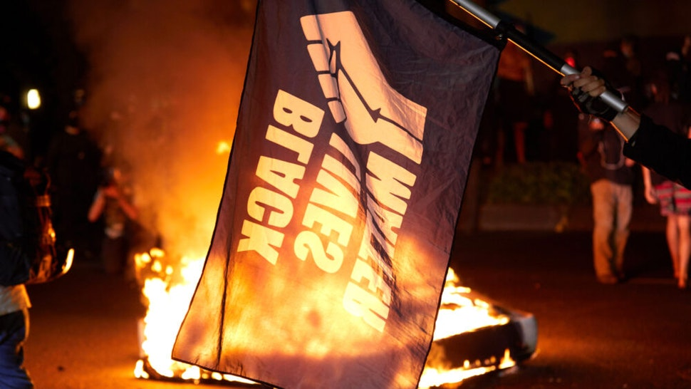 A Black Lives Matter flag waves in front of a fire at the North Precinct Police building in Portland, Oregon on September 6, 2020. - Protestors are marching for an end to racial inequality and police violence. Aaron Danielson, 39, a supporter of a far-right group called Patriot Prayer, was fatally shot August 29, 2020, in Portland, Oregon after he joined pro-Trump supporters who descended on the western US city, sparking confrontations with Black Lives Matter counter-protesters.