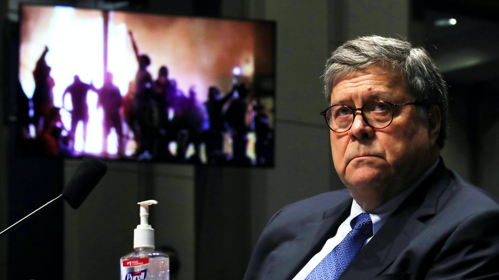 Attorney General William Barr watches a Republican Exhibit video of people rioting, during the House Judiciary Committee hearing in the Congressional Auditorium at the US Capitol Visitors Center July 28, 2020 in Washington, DC. - In his first congressional testimony in more than a year, Barr is expected to face questions from the committee about his deployment of federal law enforcement agents to Portland, Oregon, and other cities in response to Black Lives Matter protests; his role in using federal agents to violently clear protesters from Lafayette Square near the White House last month before a photo opportunity for President Donald Trump in front of a church; his intervention in court cases involving Trump's allies Roger Stone and Michael Flynn; and other issues.