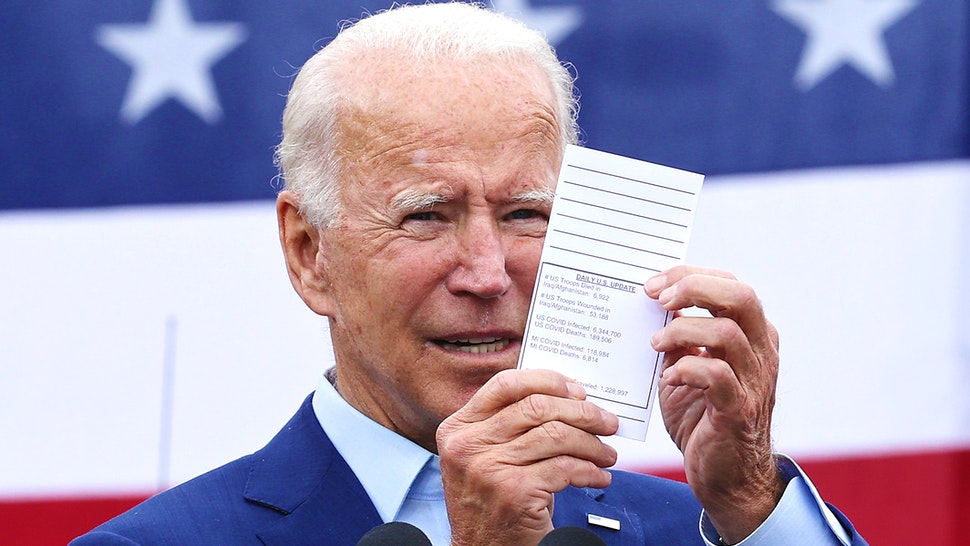 WARREN, MICHIGAN - SEPTEMBER 09: Democratic presidential nominee and former Vice President Joe Biden holds up his schedule with the latest numbers of people who have died from the coronavirus while addressing union members outside the United Auto Workers Region 1 offices on September 09, 2020 in Warren, Michigan. Biden is campaigning in Michigan, a state President Donald Trump won in 2016 by less than 11,000 votes, the narrowest margin of victory in state's presidential election history.