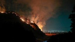 Firefighters look on from Sawpit Canyon as a control burn fires on a hillside overlooking the San Gabriel Valley as the Bobcat Fire continues to burn into its second week. (Robert Gauthier/ Los Angeles Times via Getty Images)