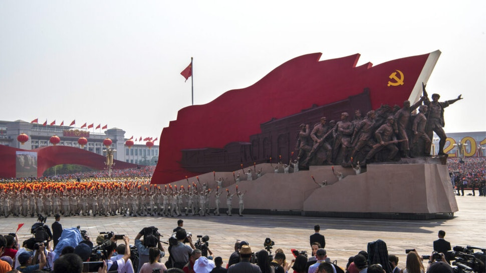 BEIJING, CHINA - OCTOBER 01: Chinese participants walk beside a Communist Party float at a parade to celebrate the 70th Anniversary of the founding of the People's Republic of China in 1949, at Tiananmen Square on October 1, 2019 in Beijing, China.