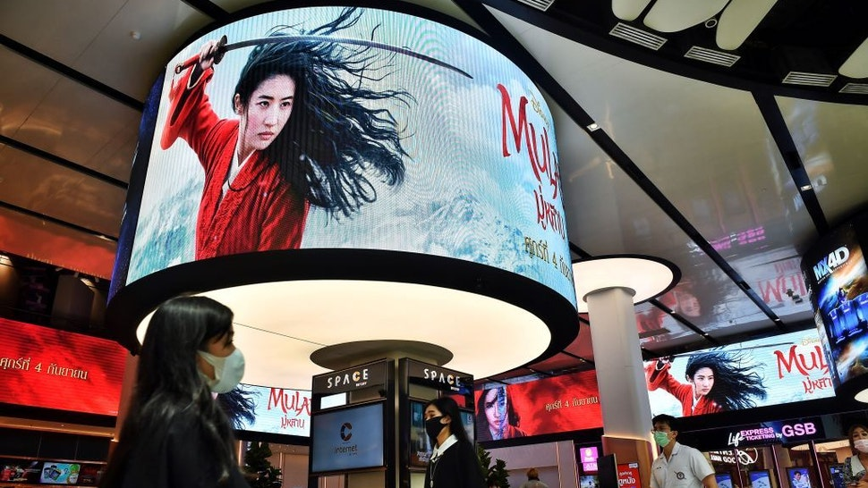 "People walk past advertising displays for Disneys Mulan film at a cinema inside a shopping mall in Bangkok on September 8, 2020. - Disney's ""Mulan"" remake is facing fresh boycott calls after it emerged some of the blockbuster was filmed in China's Xinjiang, where widespread rights abuses against the region's Muslim population have been widely documented. (Photo by Lillian SUWANRUMPHA / AFP)"