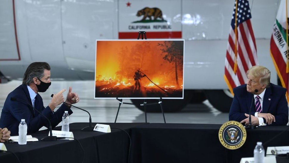 US President Donald Trump(R) speaks to California Governor Gavin Newsom(D-CA) at Sacramento McClellan Airport in McClellan Park, California on September 14, 2020 during a briefing on wildfires. (Photo by Brendan Smialowski / AFP)