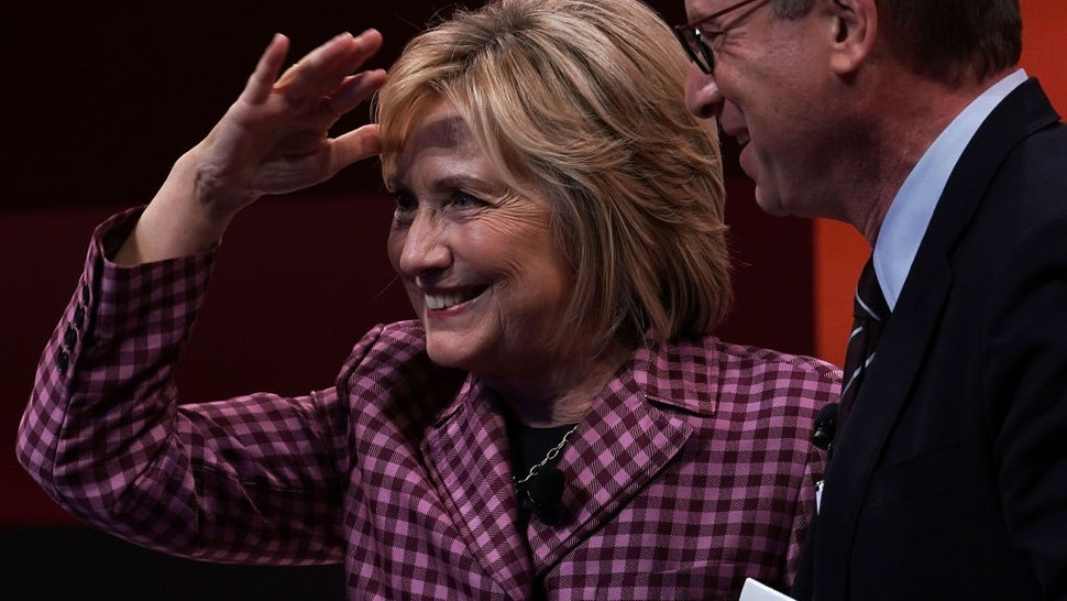 Former U.S. Secretary of State Hillary Clinton waves to audiences as Atlantic editor in chief Jeffrey Goldberg looks on after a discussion during the 2018 Atlantic Festival October 2, 2018 in Washington, DC.