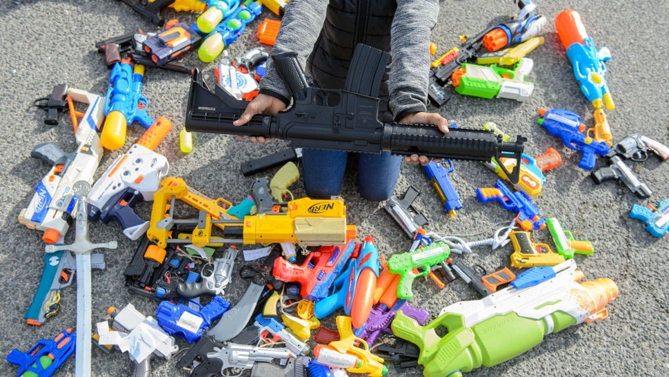 """A boy is holding a toy gun in his hands on the occasion of an action day of the Nuremberg Toy Museum as part of the worldwide """"Children's Conferences"""" in the inner courtyard of the Congress Hall in Nuremberg."""