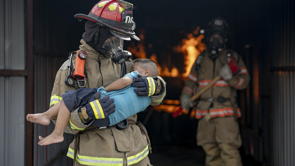 Brave Fireman of a Burning Building and Holds Saved boy in His Arms. Open fire and one Firefighter in the Background.