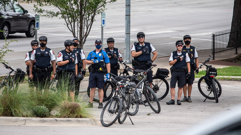 """Police officers hold their hands over their hearts as a demonstrator sings the National Anthem during a """"Bar Lives Matter"""" protest in Austin, Texas, U.S., on Tuesday, June 30, 2020."""