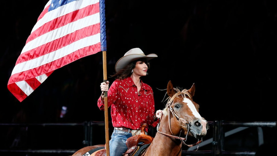 South Dakota's Governor Kristi Noem holds the U.S flag riding a horse during the Monster Energy Team Challenge, on July 11, 2020, at the Denny Sanford PREMIER Center, Sioux Falls, SD.