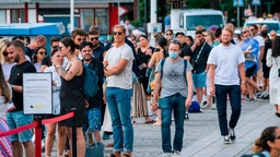 A man wearing a protective mask walks next to travellers as they queue up to board a boat at Stranvagen in Stockholm on July 27, 2020, during the novel coronavirus