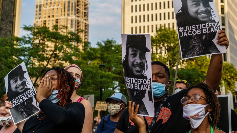Protesters hold signs outside the Minneapolis 1st Police precinct during a demonstration against police brutality and racism on August 24, 2020 in Minneapolis, Minnesota.