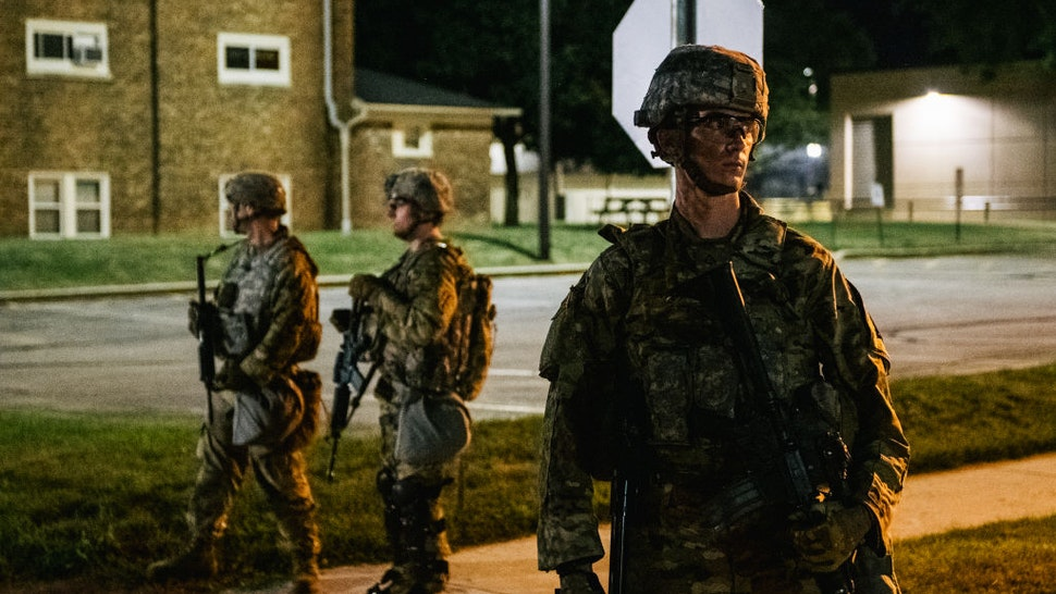 KENOSHA, WI - AUGUST 27: National Guard troops stand guard inside of a fenced area that surrounds several government buildings on August 27, 2020 in Kenosha, Wisconsin. Wisconsin Gov. Tony Evers approved a request for an additional 500 National Guard troops to be deployed into Wisconsin on August 26. Many arrests have been made with the additional presence of law enforcement. Civil unrest has occurred in multiple states after the shooting of Jacob Blake, 29, on August 23. Blake was shot multiple times in the back by Wisconsin police officers after attempting to enter into the drivers side of a vehicle. (Photo by Brandon Bell/Getty Images)