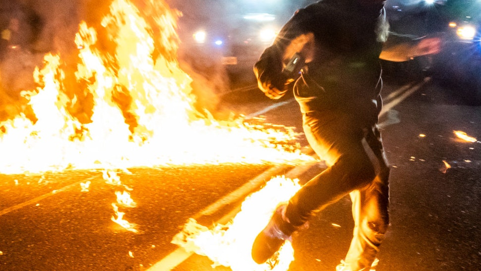 A protester, whos feet caught fire after a molotov cocktail exploded on him, runs toward a medic during a protest against police brutality and racial injustice on September 5, 2020 in Portland, Oregon. Portland has seen