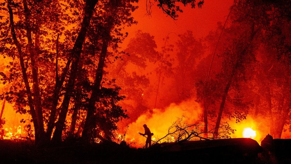 A firefighter douses flames as they push towards homes during the Creek fire in the Cascadel Woods area of unincorporated Madera County, California on September 7, 2020.