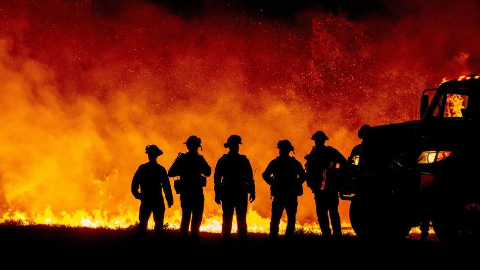 Butte County firefighters watch as flames quickly spread across a road at the Bear fire in Oroville, California on September 9, 2020. - Dangerous dry winds whipped up California's record-breaking wildfires and ignited new blazes, as hundreds were evacuated by helicopter and tens of thousands were plunged into darkness by power outages across the western United States. (Photo by JOSH EDELSON / AFP) (Photo by JOSH EDELSON/AFP via Getty Images)