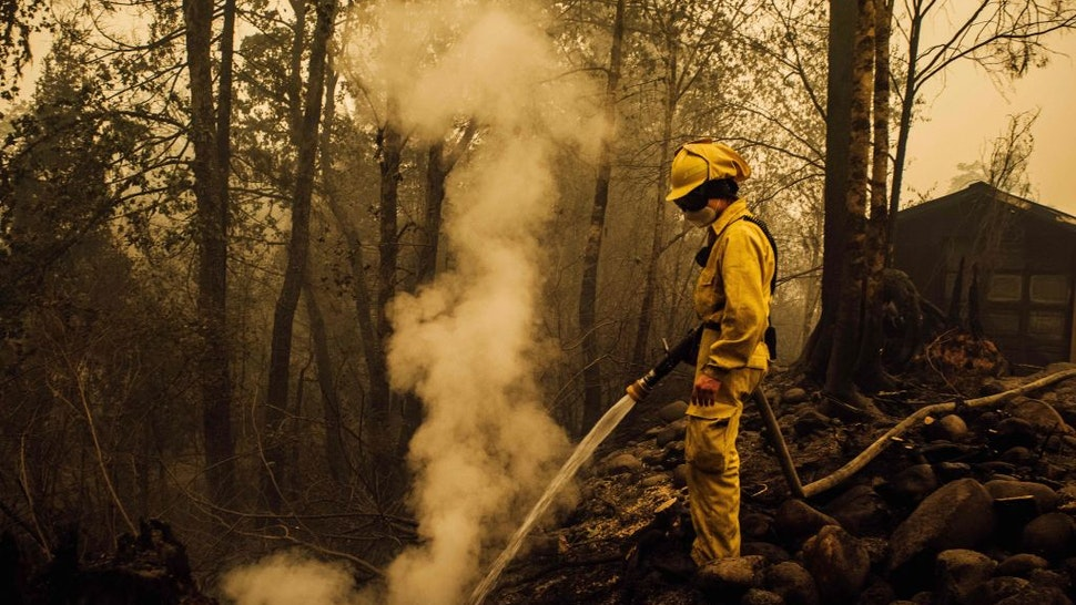 Volunteer firefighter Jacob Ruthrock puts out embers from a fire in Gates, Oregon, on September 10, 2020. - California firefighters battled the state's largest ever inferno on September 10, as tens of thousands of people fled blazes up and down the US West Coast and officials warned the death toll could shoot up in coming days. At least eight people have been confirmed dead in the past 24 hours across California, Oregon and Washington, but officials say some areas are still impossible to reach, meaning the number is likely to rise. (Photo by Kathryn ELSESSER / AFP) (Photo by KATHRYN ELSESSER/AFP via Getty Images)