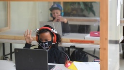 Students follow along remotely with their regular school teacher's online live lesson from separated by plastic barriers at STAR Eco Station Tutoring & Enrichment Center on September 10, 2020 in Culver City, California.