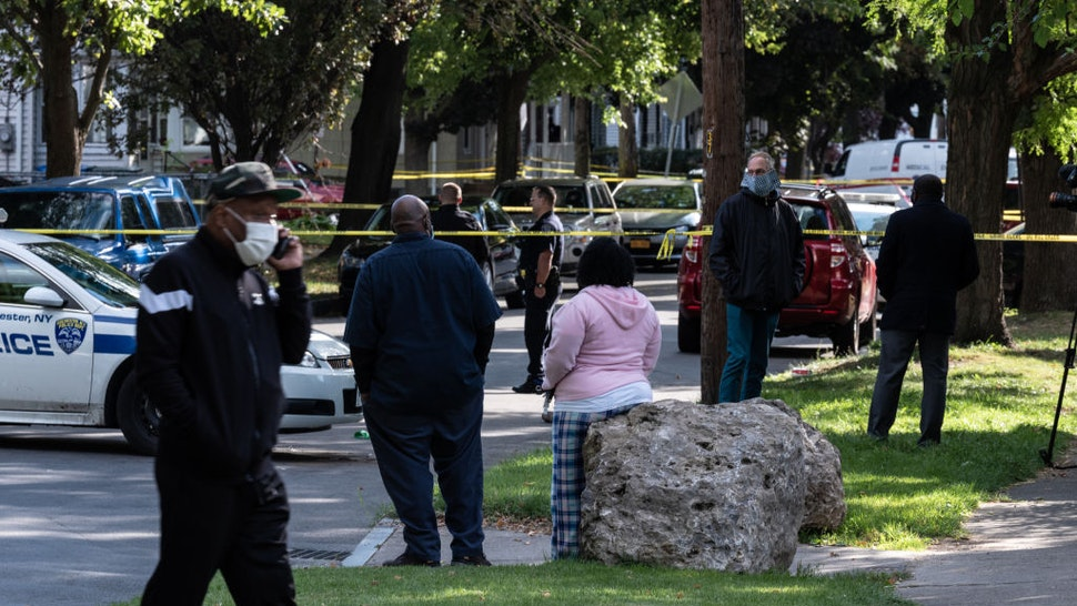 People look on as police investigate a crime scene after a shooting at a backyard party on September 19, 2020, Rochester, New York.